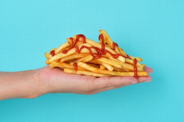 une main remplie de frites ketchup