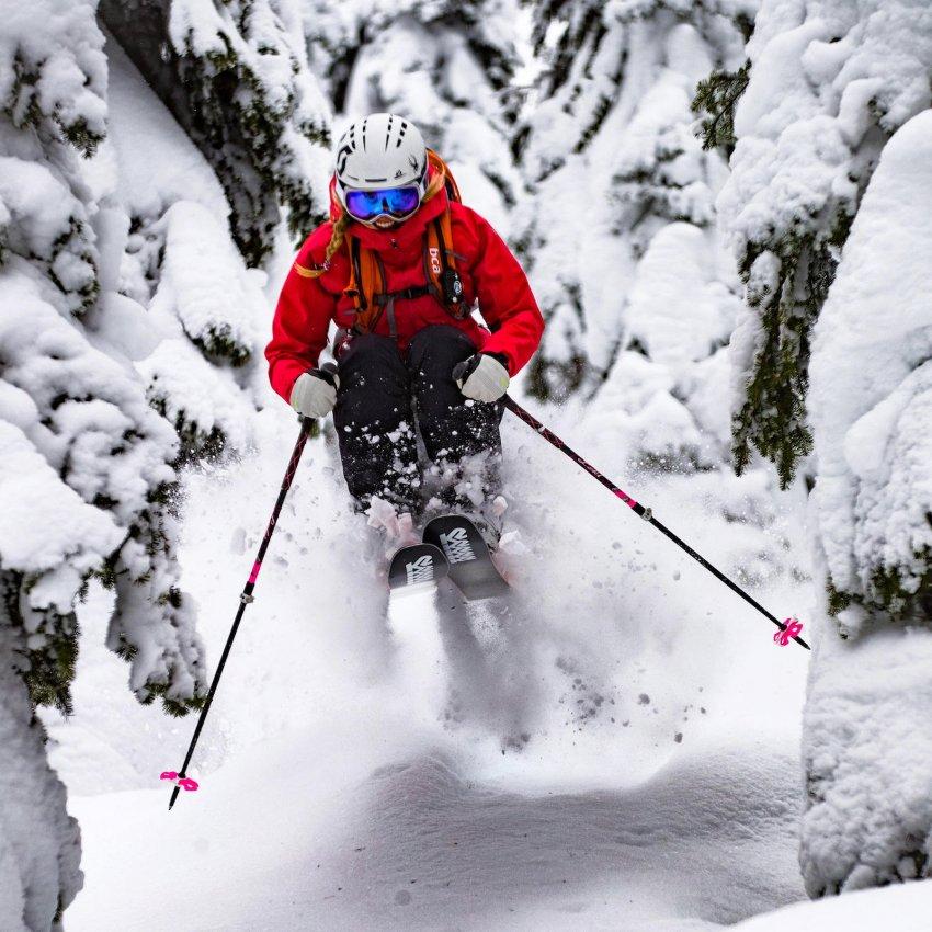 Amie Engerbretson en backcountry dans la poudreuse entre forêt et barre rocheuse