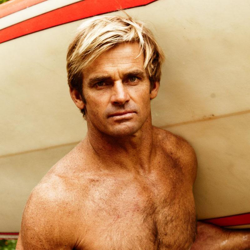 Lair Hamilton porte sa planche de surf