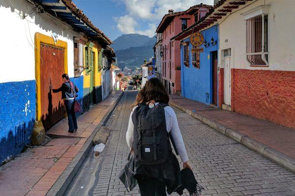 Une backpackeuse de dos dans une rue colorée