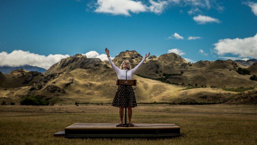 Kristine Tompkins lève les bras sur une estrade au milieu de la pampa