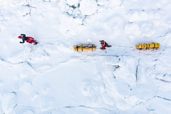 Deux personnes tirent des traîneaux sur la neige