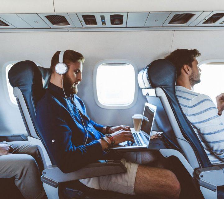 Un hipster portant un casque travaille sur son ordinateur dans un avion