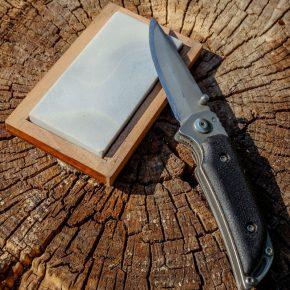 Un couteau de poche posé sur une pierre à aiguiser sur une souche d'arbre.