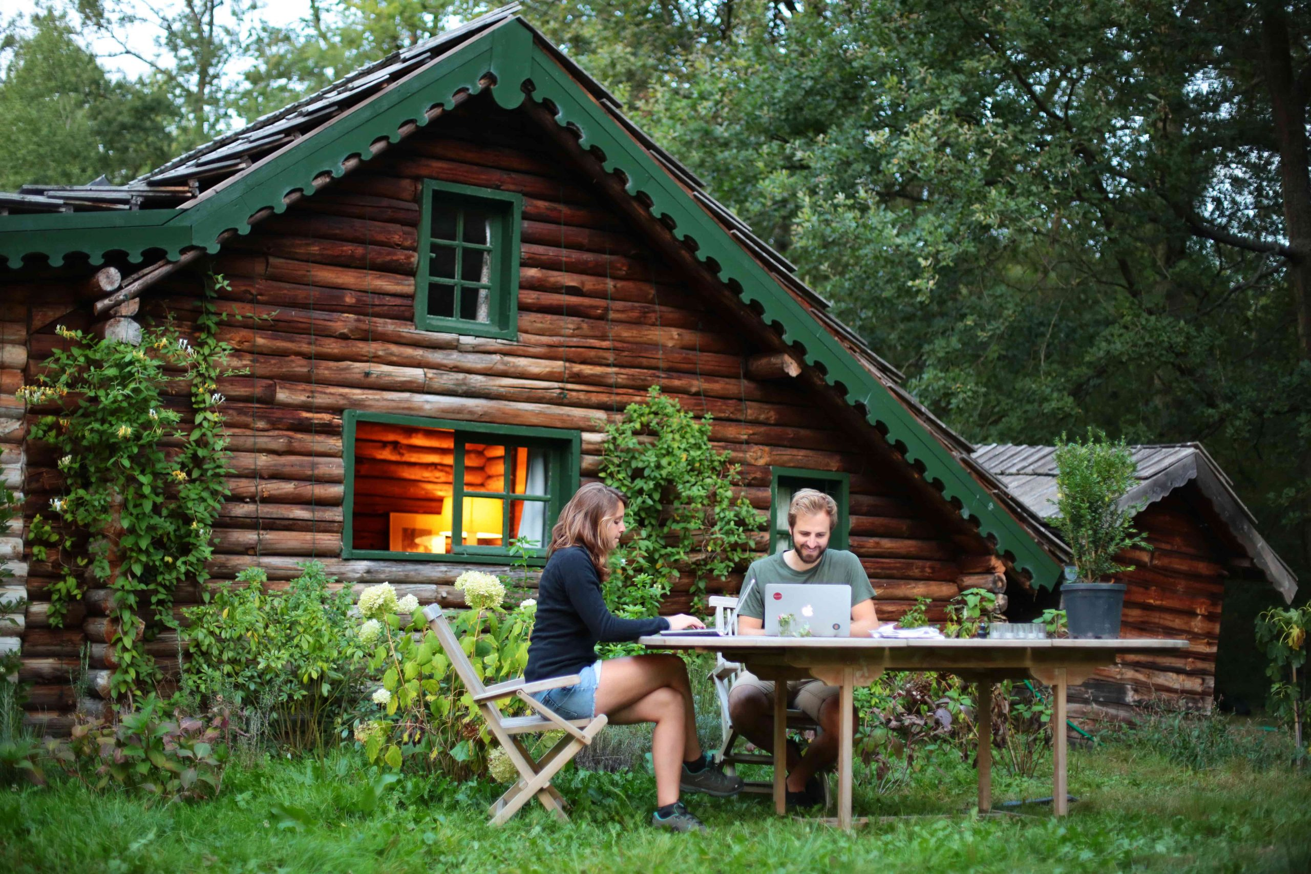 Un couple travaille dehors devant un gîte en bois