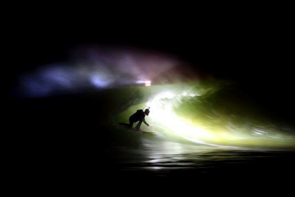 Un surfeur test la frontale Black Swan de nuit.
