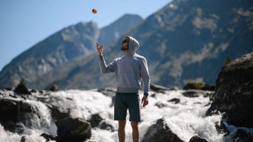 Un homme devant un torrent lance une pomme en l'air