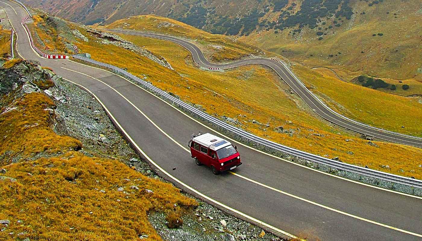 Un Van rouge roule sur une route de montagne