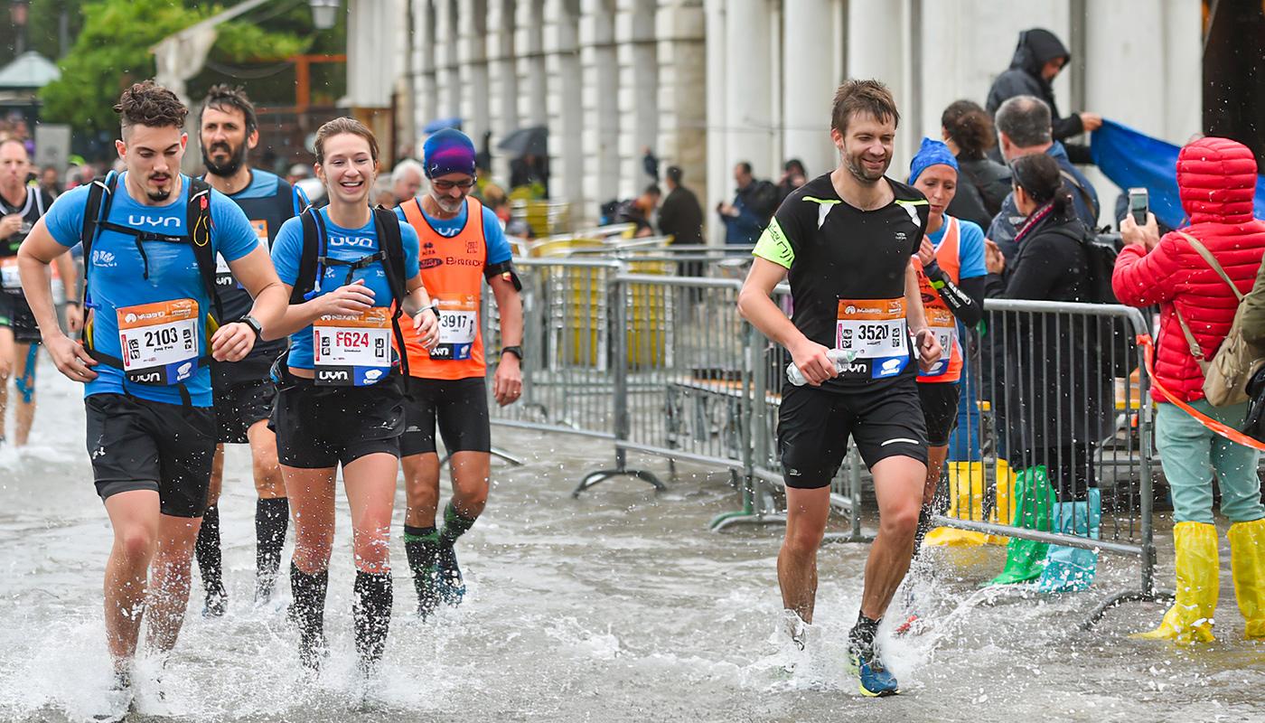 Les coureurs les pieds dans l'eau au Marathon de Venise