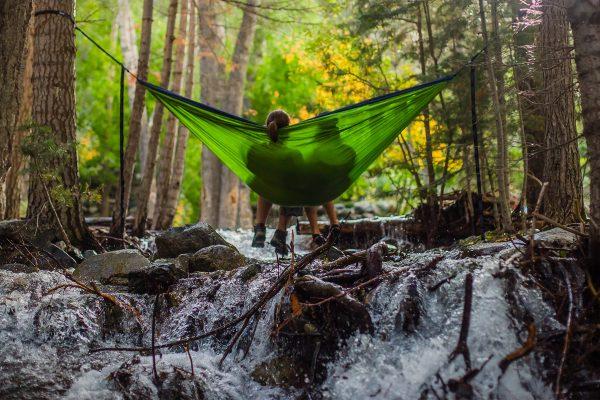 Deux personnes se reposant au dessus d'une rivière en forêt