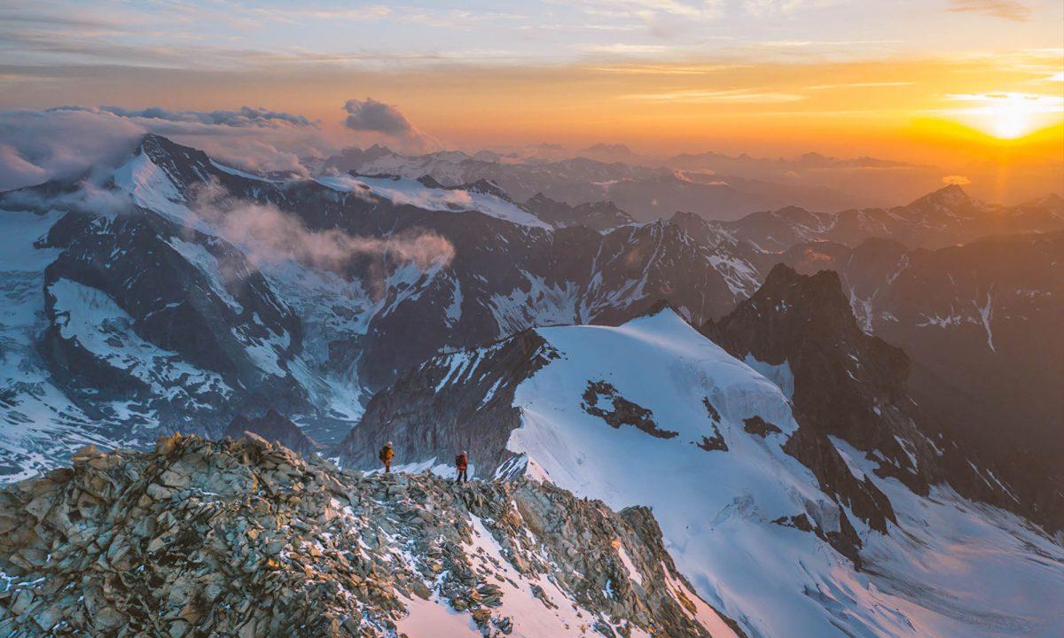alpinistes marchant sur un crête au couché du soleil
