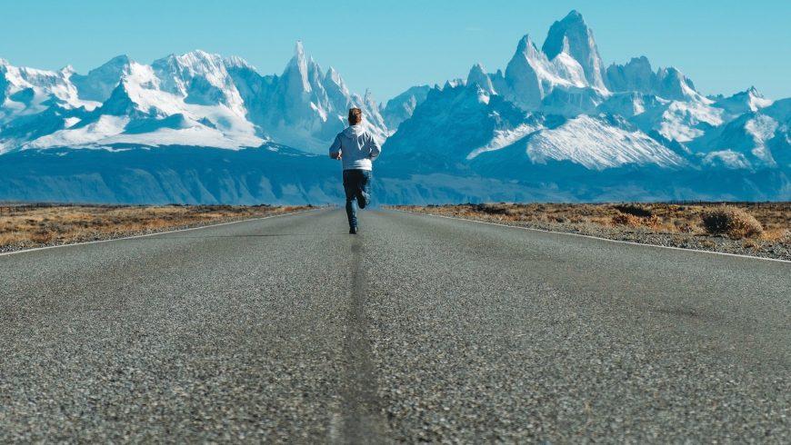 homme courant sur la route vers des montagnes enneigées Andrea Leopardi/Unsplash