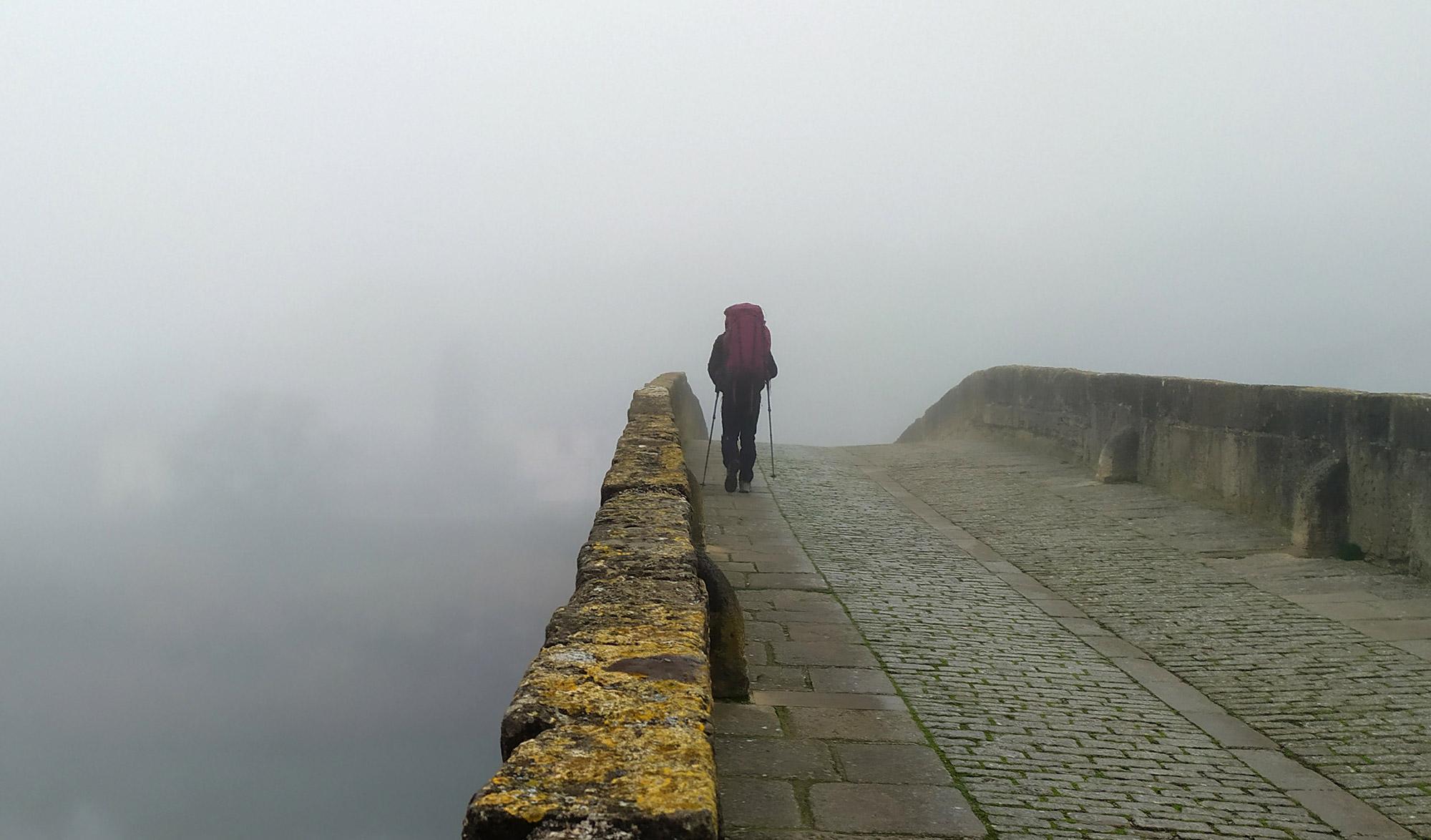 randonneurs sur un pont avec du brouillard