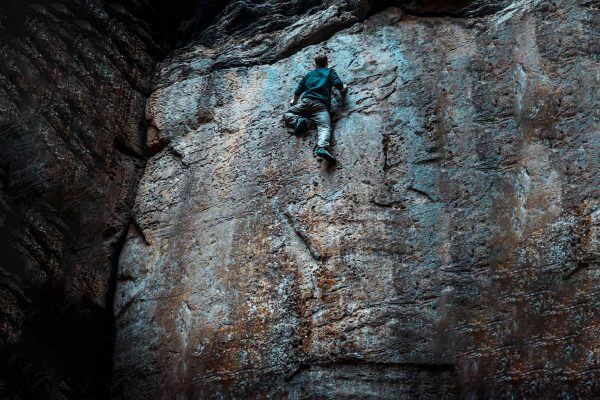 grimpeur en free solo sur un mur sombre