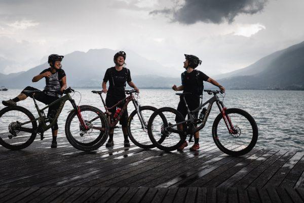 3 rideuses sur un ponton d'Annecy avec leur VTT